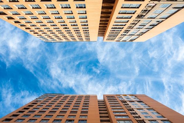 Os edifícios verticais das casas com fundo do céu azul fotografaram da terra.