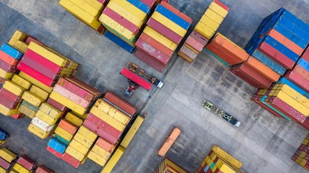 Os empilhadores do alcance da vista aérea movem recipientes em um terminal do frete, em um terminal de recipiente industrial e em uma área dos recipientes de armazenamento.