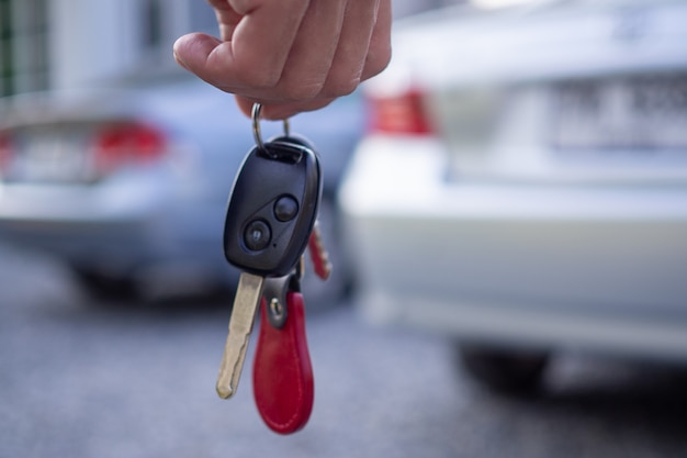 Os empregados da venda enviam as chaves do carro aos turistas após fazerem um aluguel. alugue ou compre carro conceito