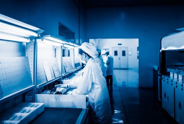 Os empregados do traje de laboratório branco trabalham na fábrica