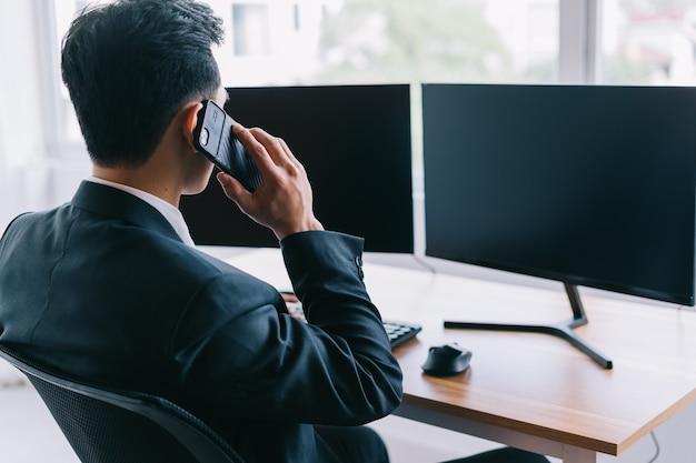Os empresários asiáticos estão concentrados em trabalhar enquanto estão ao telefone. um computador com duas telas em branco