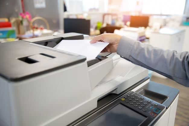 Os empresários colocam papel na copiadora.