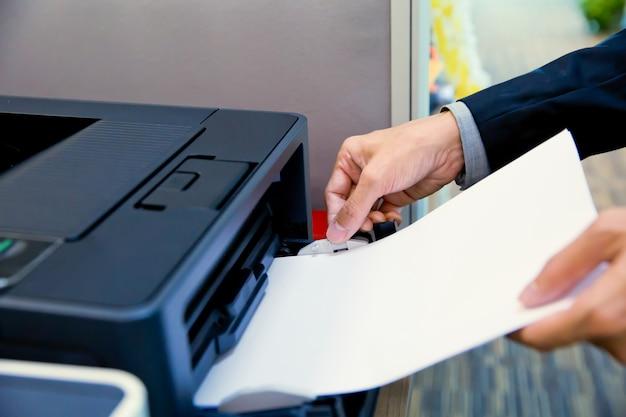 Os empresários colocam um papel nas fotocopiadoras.