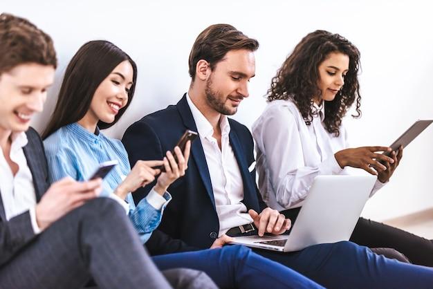 Os empresários com gadgets sentados no fundo da parede branca