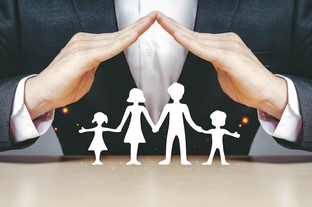 Os empresários de seguros asiáticos usam as mãos para proteger as famílias de papel branco que desfrutam em casa.