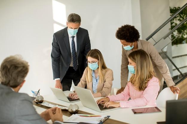 Os empresários do grupo têm uma reunião e trabalham no escritório e usam máscaras como proteção contra o coronavírus