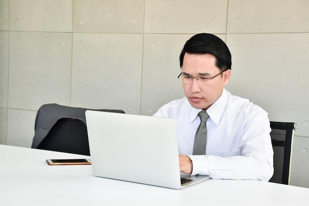 Os empresários estão estressados com o trabalho duro sentado no computador com o telefone.