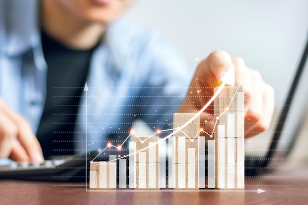 Os empresários estão verificando gráficos de ações e planejando suas estratégias de negociação de ações para o pico de crescimento.