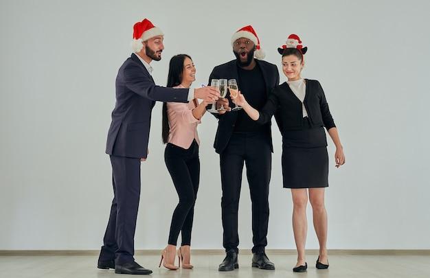 Os empresários felizes com chapéu de papai noel bebendo champanhe