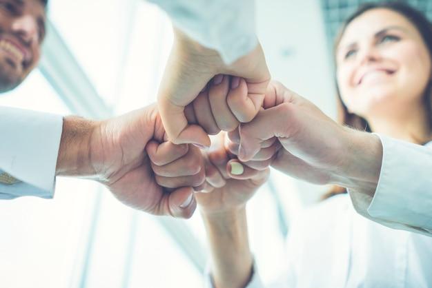 Os empresários felizes gesticulam com o punho