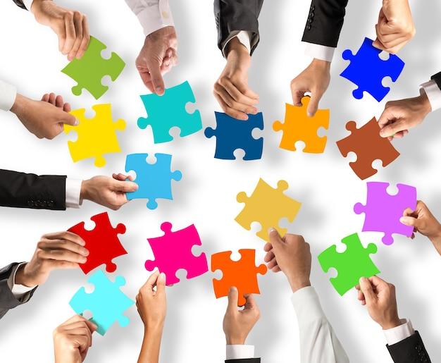 Os empresários juntam-se às coloridas peças do puzzle. conceito de trabalho em equipe e integração