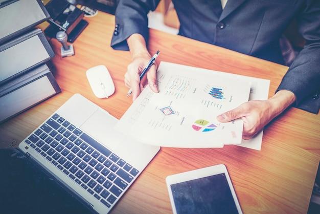 Os empresários são analisados dados do relatório usando o smartphone e computador portátil.