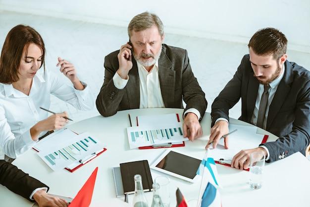Os empresários trabalhando juntos na mesa. o conceito de reunião ou cúpula