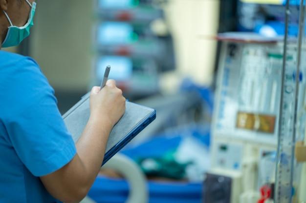 Os enfermeiros estão verificando o funcionamento da máquina de hemodiálise antes de usá-la em pacientes com insuficiência renal crônica.