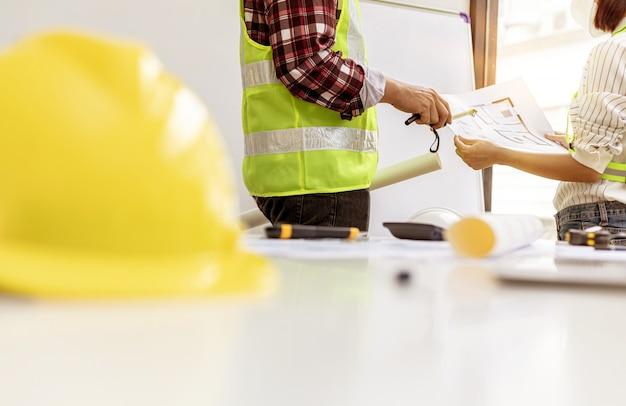 Os engenheiros arquitetos estão de prontidão para examinar as plantas das casas projetadas, eles se reúnem para planejar a construção e modificar alguns dos projetos. idéias de design e design de interiores.