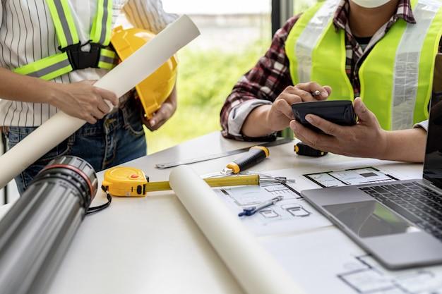 Os engenheiros arquitetos estão usando o telefone na reunião para discutir os materiais de construção, eles se reúnem para planejar a construção e consertar alguns projetos. idéias de design e design de interiores.