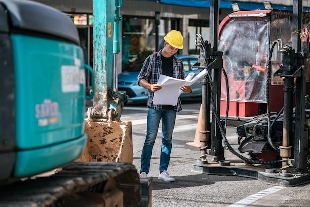 Os engenheiros civis trabalham em grandes condições de estradas e máquinas.