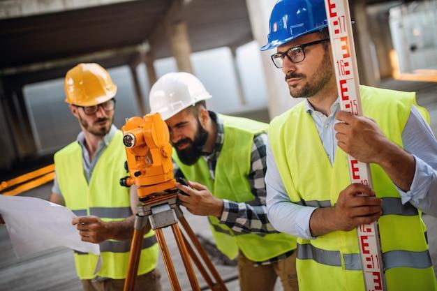 Os engenheiros de construção discutem com os arquitetos na construção ou no canteiro de obras