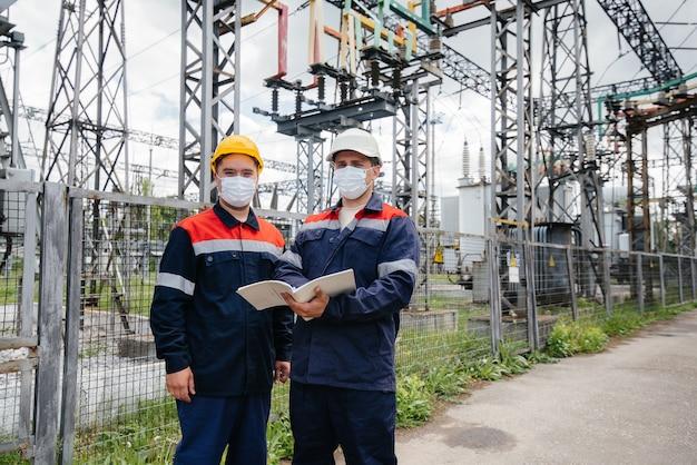 Os engenheiros de energia inspecionam os equipamentos da subestação