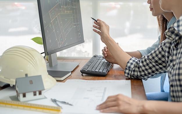 Os engenheiros discutem uma planta enquanto verificam as informações em um computador tablet em um escritório.