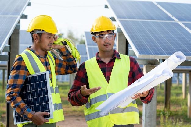 Os engenheiros elétricos com blueprint estão verificando e reparando os conceitos de energia solar, energia renovável e energia solar.