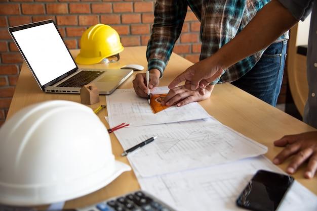 Os engenheiros estão apontando diretamente para o plano de construção para apresentar e discutir
