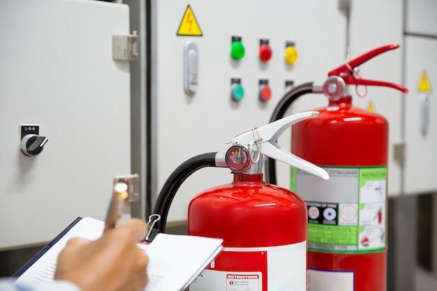 Os engenheiros estão verificando e inspecionando um extintor de incêndio na sala de controle de incêndio por segurança.