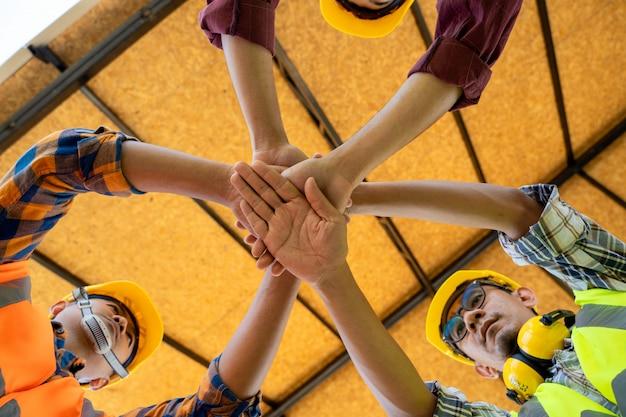 Os engenheiros juntam as mãos para construir projetos de sucesso, trabalho em equipe do engenheiro de trabalho em equipe trabalham juntos em um canteiro de obras, conceito de trabalho em equipe.