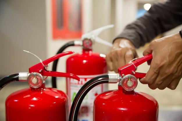 Os engenheiros puxam o pino de segurança dos extintores de incêndio.
