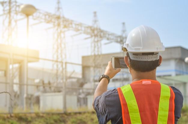 Os engenheiros usam telefones celulares para fotografar postes de eletricidade de alta tensão contra o fundo da subestação.