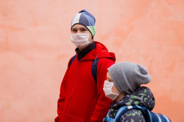 Os escolares com máscaras protetoras na rua