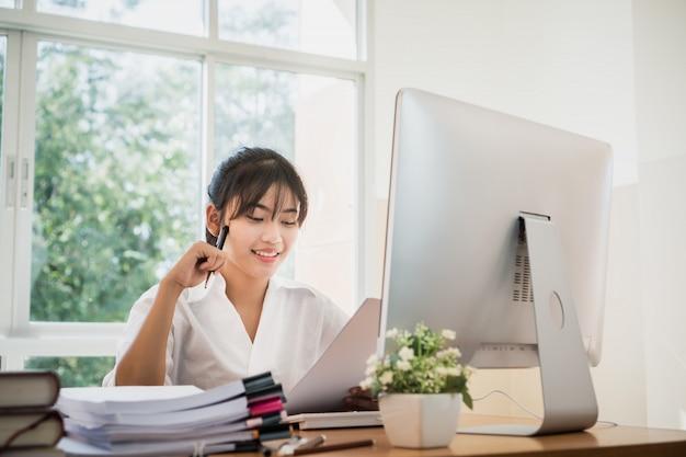 Os escritórios asiáticos da mulher de negócios verificam trabalhando para a pilha inacabada dos originais de papéis de documento com no escritório ocupado do computador