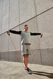 Os esportes musculares novos consideráveis equipam o exercício fora no por do sol com elástico.