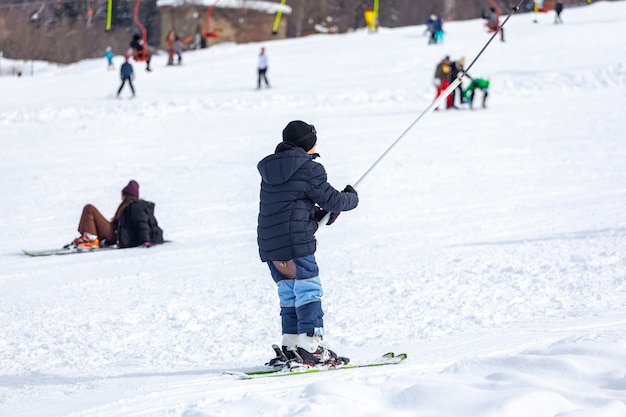 Os esquiadores que esquiam escalam um jugo em uma montanha. pista de esqui leve em bakuriani