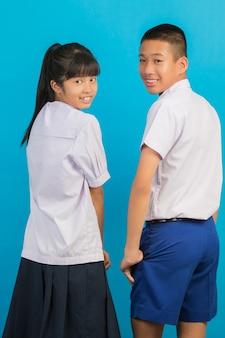 Os estudantes asiáticos novos e os estudantes masculinos asiáticos estão juntos em um azul.