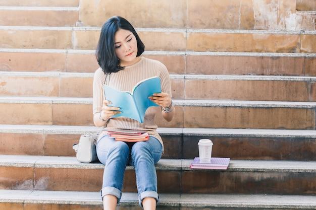 Os estudantes do adolescente da jovem mulher com livros sentam-se na escada