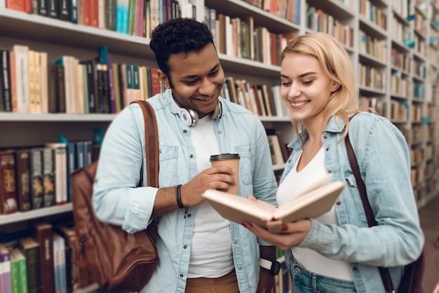 Os estudantes estão à procura de livros na grande biblioteca.