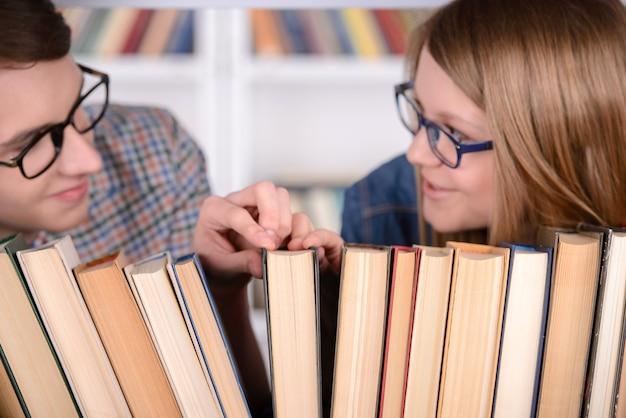 Os estudantes felizes olham o livro para ler na biblioteca.