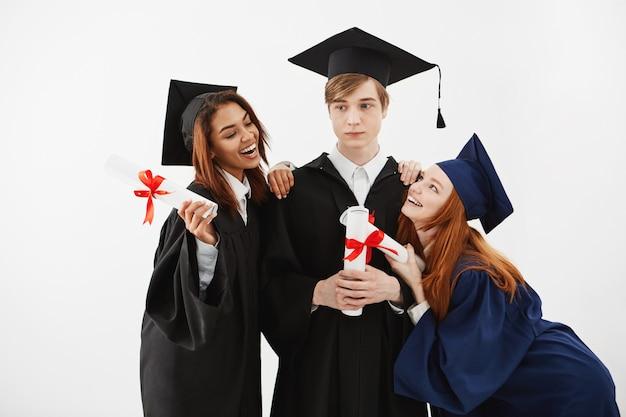 Os estudantes internacionais graduam-se alegrando posando posando.