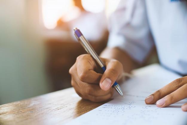 Os estudantes que escrevem a pena à disposição que faz exames respondem às folhas exercitam na sala de aula com esforço.