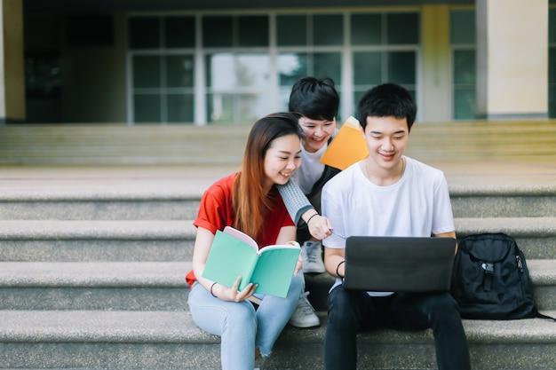 Os estudantes universitários ajudam a trabalhar juntos, eles procurando por informações de um laptop.
