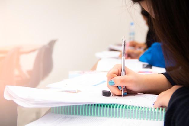 Os estudantes universitários fazem testes, testes ou estudos com o professor em uma grande sala de aula. alunos de uniforme na escola educacional de sala de aula de exame.