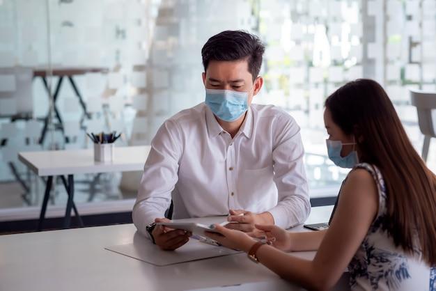 Os executivos da equipe asiática analisam a colaboração usando um tablet no escritório usando máscaras.