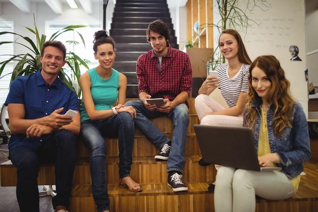 Os executivos de negócios que usa a tabuleta digital, telefone celular e lapto