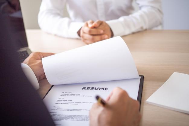 Os executivos estão entrevistando novos funcionários, com base em currículos, experiência de trabalho e atitude em relação ao trabalho na empresa.