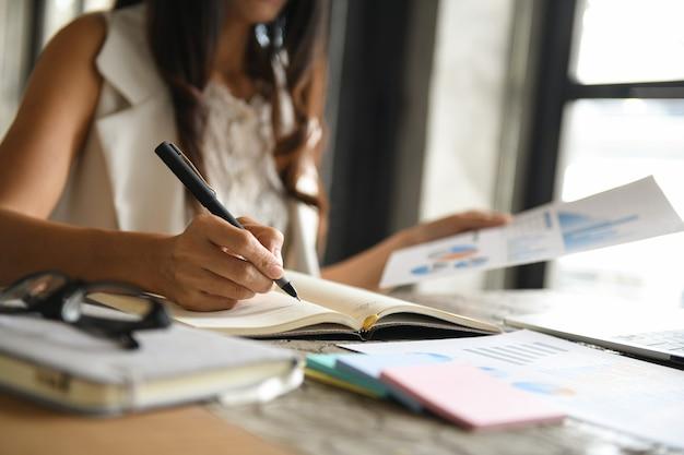 Os executivos estão verificando dados de gráficos e fazendo anotações.