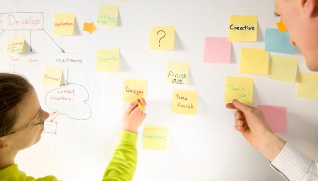 Os executivos que encontram-se no cargo do escritório colorido anotam etiquetas na placa. conceito de brainstorming.
