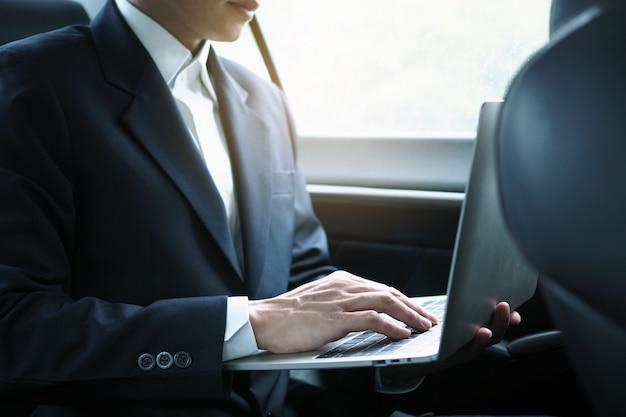 Os executivos usam laptops para trabalhar enquanto viajam e sentam dentro do carro.