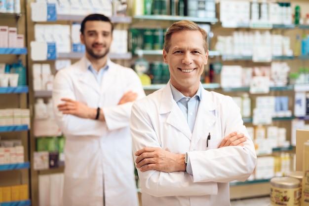 Os farmacêuticos masculinos na farmácia.
