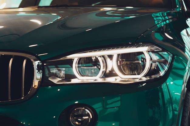 Os faróis do close up do carro moderno durante acendem a luz na noite.